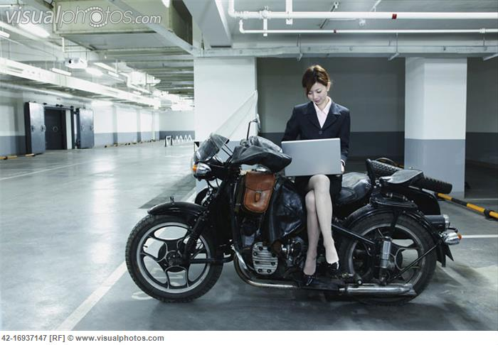 Businesswoman on Motorbike Using Laptop