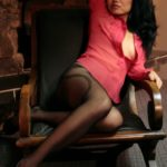 Aurora is posing on a chair in black patterned pantyhose.