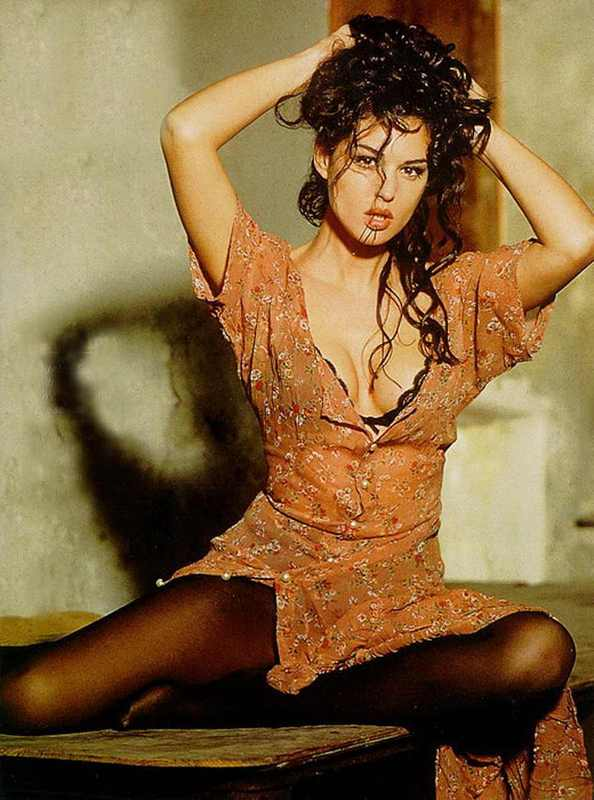 Monica Bellucci in black pantyhose in a sexy pose with a cleavage