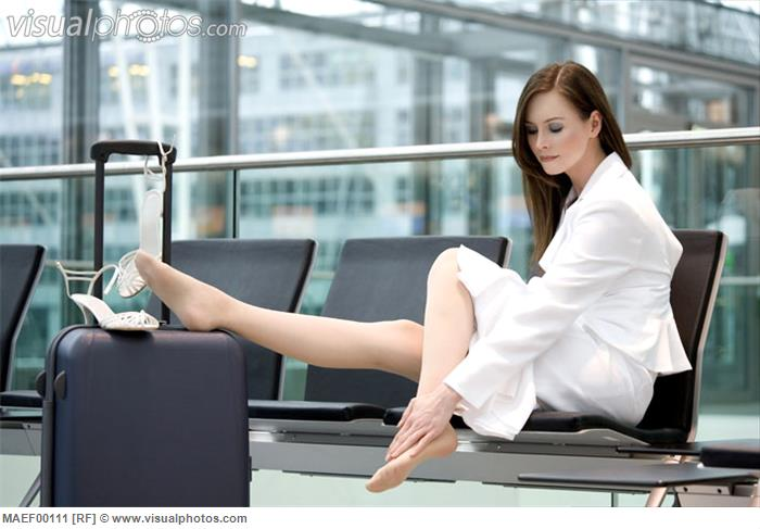 Business woman sitting in airport lounge, feet on suit case
